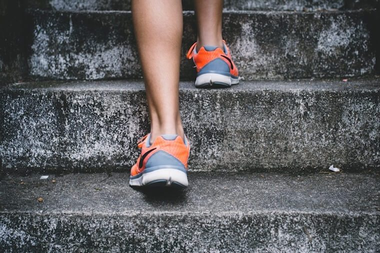 Image of a person wearing running shoes walking up stairs