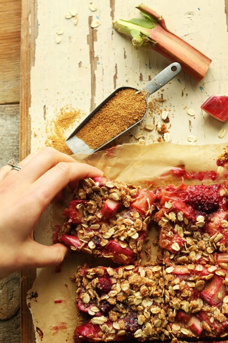 A hand grabbing a bar of strawberry rhubarb crumble bars.