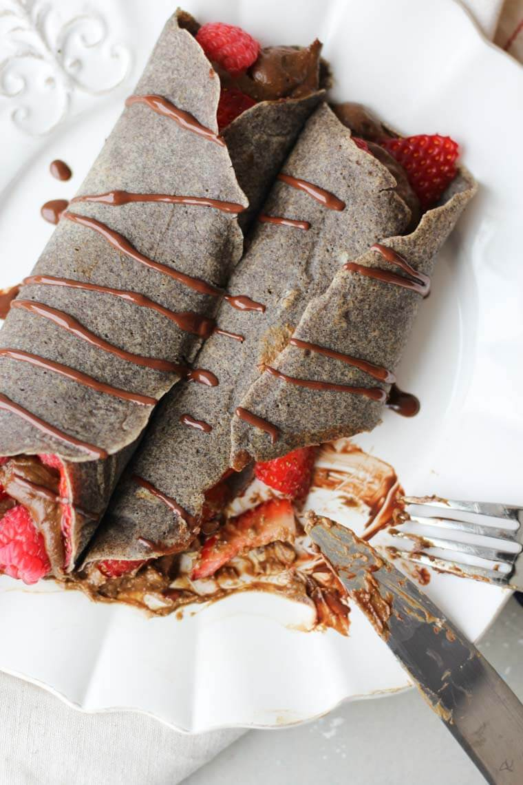 A chocolate buckwheat crepe being cut with a knife and fork.