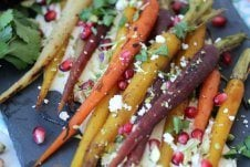 A close up of roasted carrots with pomegranate seeds and cheese sprinkled on top.