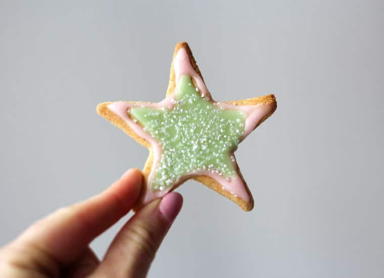 A hand holding a star shaped almond sugar cookies.