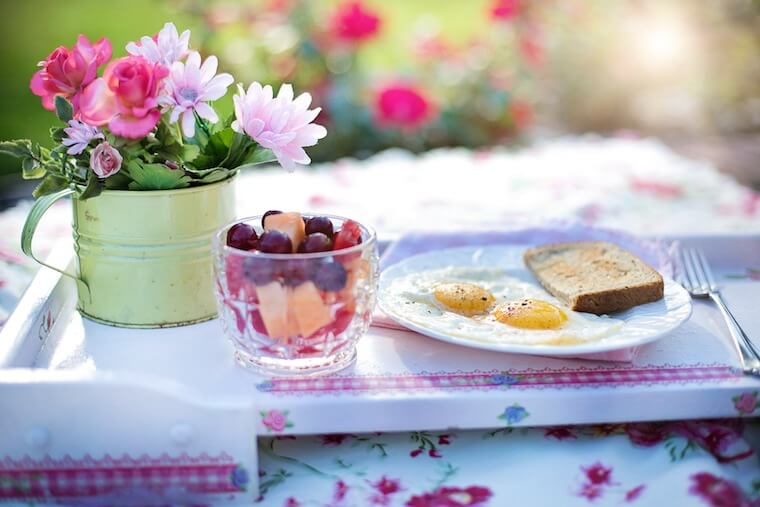 A photo of a glass filled with fruit on a table with a plate of eggs beside it.