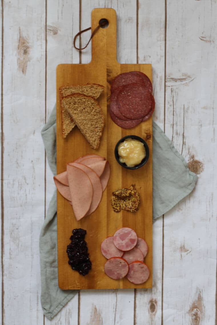 A wooden serving platter with charcuterie on it, such as cheese, sliced meats, bread slices, and nuts.
