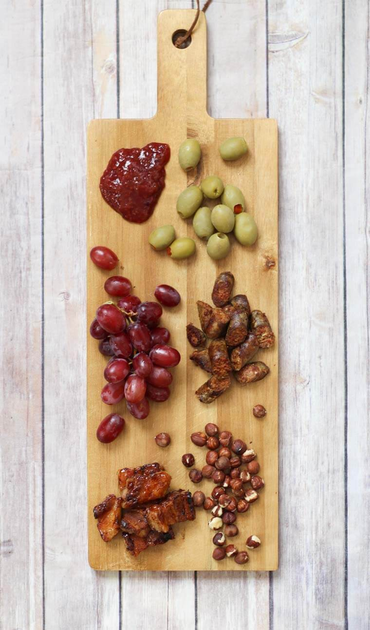 A wooden serving board with jam, olives, grapes, meat,  and nuts.