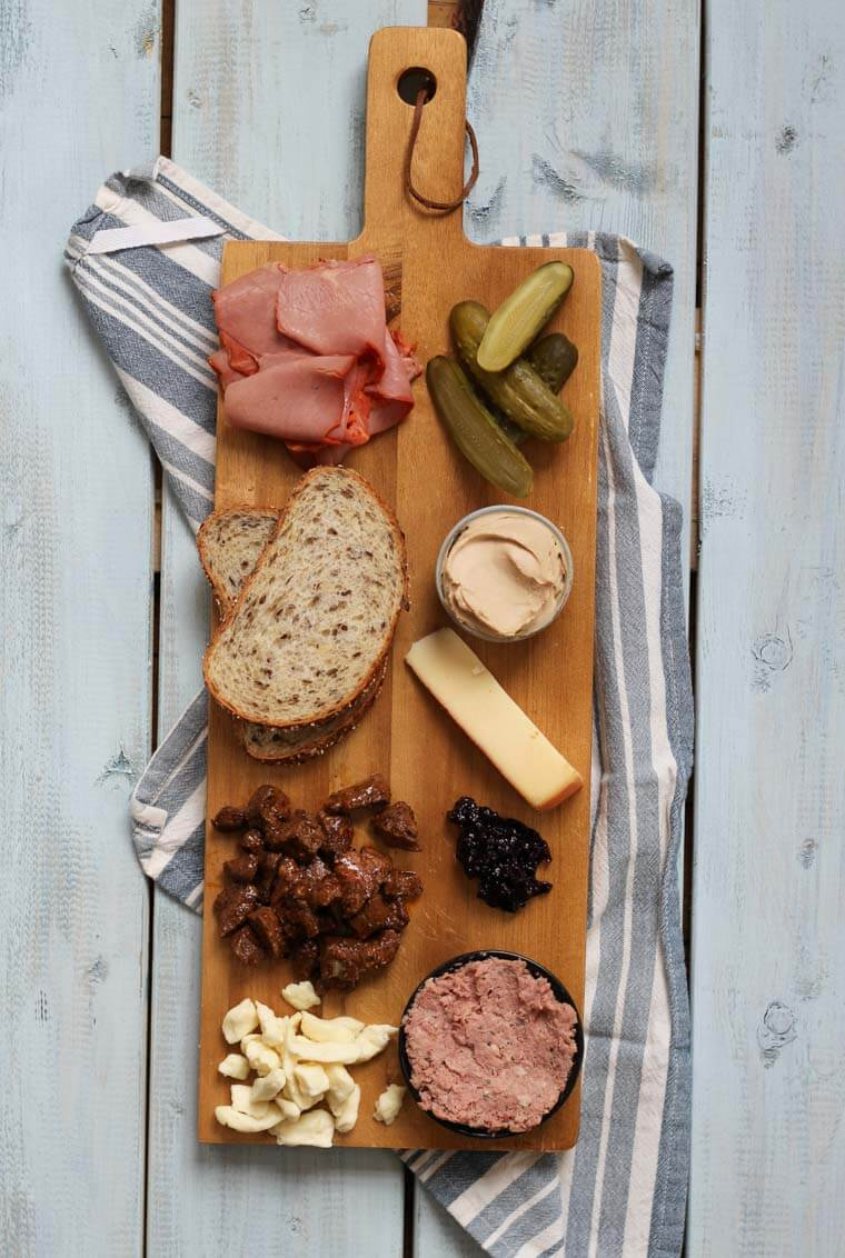 A wooden serving platter with charcuterie on it, such as cheese, meats, bread slices, pickles, and nuts.