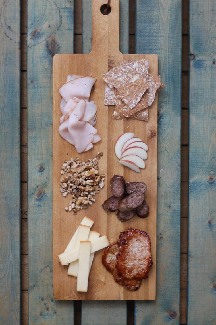 A wooden serving platter with charcuterie on it, such as cheese, meats, apple slices, and nuts.