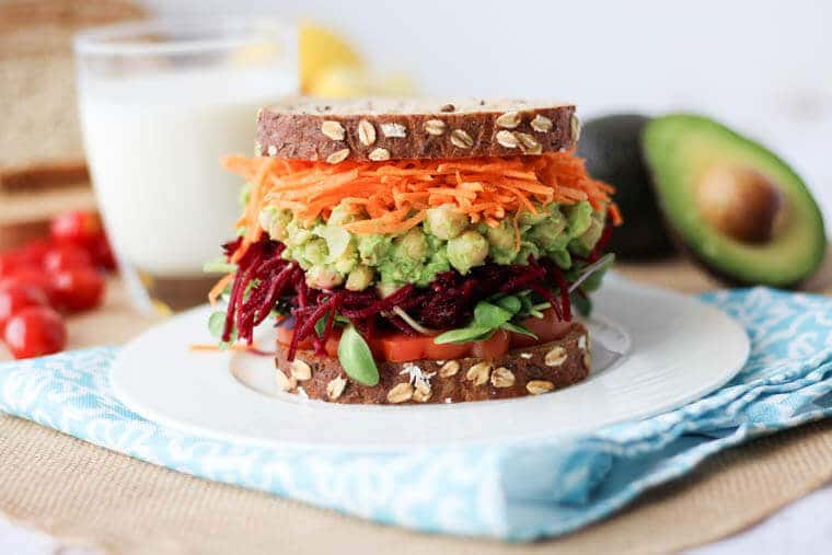 close up of vegan avocado and chickpea salad sandwich on brown bread served with fresh vegetables on a blue cloth