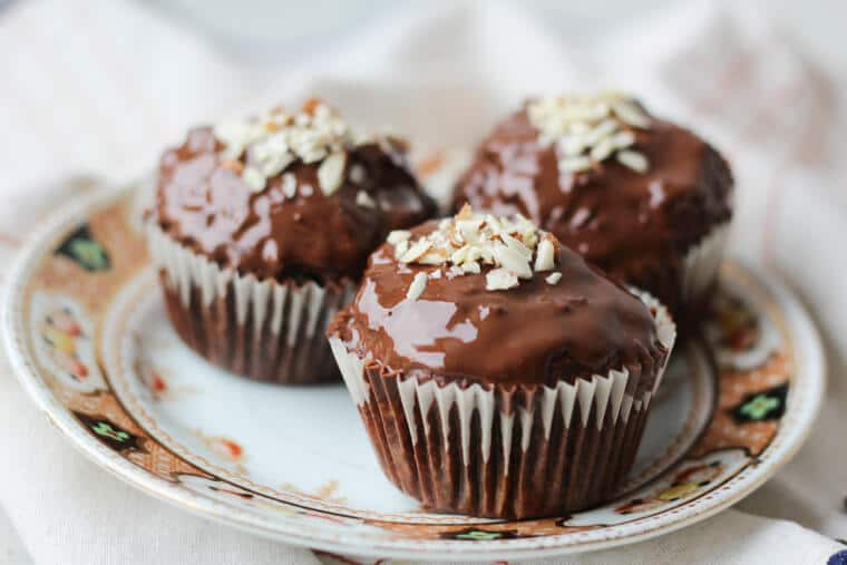 A plate of three chocolate cherry almond muffins with a chocolate glaze with almonds on top.