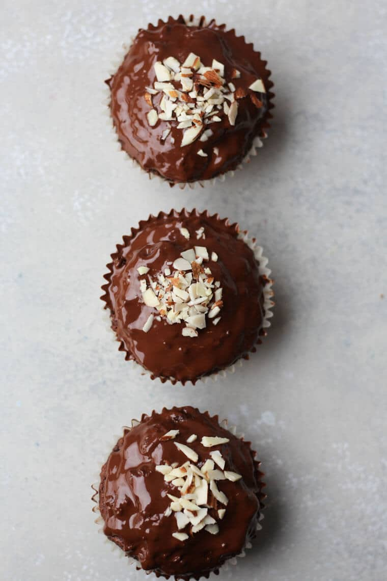 An overhead photo of a chocolate muffin with chocolate glaze with crushed almonds on top.
