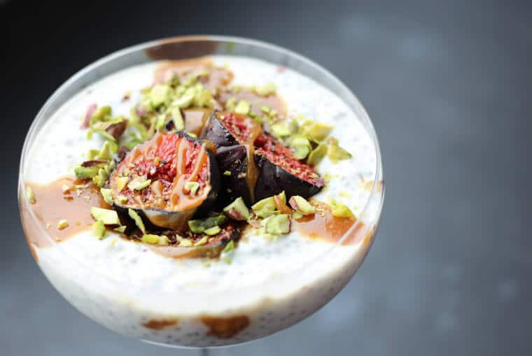 An angled photo of a roasted fig chia pudding with tahini date caramel on top.