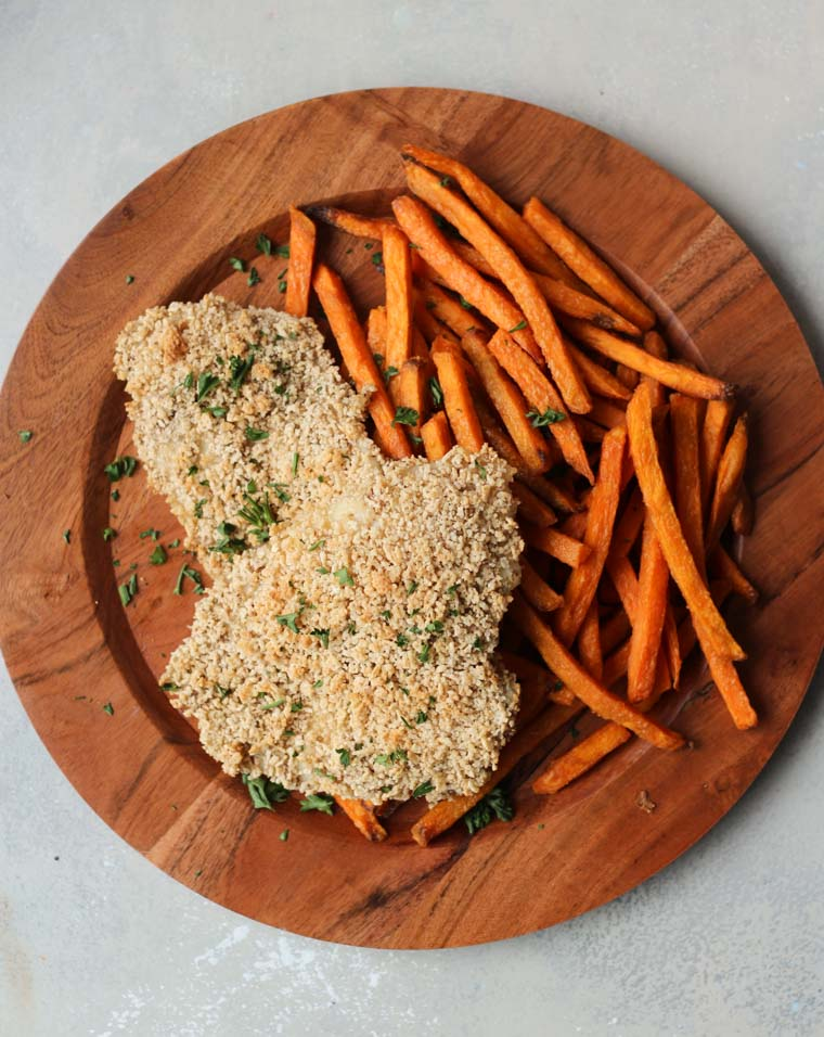 "Gluten Free Baked Panko Fish and Chips with Sweet Potato Fries These Gluten Free Baked Panko Fish and Chips with Sweet Potato Fries are a healthy alternative to the classic pub staple or Friday night take out! Serves 4 Main dish British Cook time: 30 min Prep time 15 min 410 calories Panko Fish: ¼ cup ground flax seed ½ cup + 2 tablespoons water 1/3 cup gluten free oats 1/2 teaspoon table salt ¼ teaspoon cracked black pepper ¼ tsp chili powder 4 cups Chex cereal 4 thin white fish filets Fleur de sel, for sprinkling Sweet Potatoes: 2 medium sweet potatoes, cut into ¼"" thin fries 2 tbsp. extra virgin olive oil 1/2 tsp sea salt 1/4 tsp cracked black pepper ¼ tsp chili powder Fleur de sel, for sprinkling Preheat oven to 450 F. Lightly grease two baking sheets and place them in the oven to preheat. To make the flax egg, mix the flax and water together in a small bowl and let it sit in the fridge for 20-30 minutes until it reaches a gloopy egg-like consistency. Place the oats in a small food processor and pulse until they reach a flour-like consistency. In another bowl, mix together the oat flour, salt, pepper and chili. Add the chex cereal to the food processor and pulse until it breaks into crumbs. Transfer to a third bowl. Dip the fish filets into the flour, then transfer them to the flax egg until well coated. Finally, coat them in the Chex panko crumbs. Transfer to one of the preheated baking sheets. Meanwhile, mix the potatoes with the oil, sea salt, pepper and chili. Transfer to the other large baking sheet in a single layer and bake for 25 to 30 minutes, turning once for even browning. About 15 minutes into your sweet potatoes cooking, add in a second sheet with the fish and bake for about 12 to 15 minutes or until cooked through and just slightly starting to brown. Chex, like panko, doesn't get super golden brown so you'll likely just see a slight golden hue. While still hot, top the fish and chips with a pinch of fleur de sel."