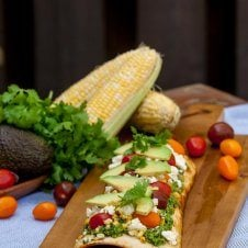 A tasty corn cilantro pesto grilled pizza with pesto, corn, and feta.
