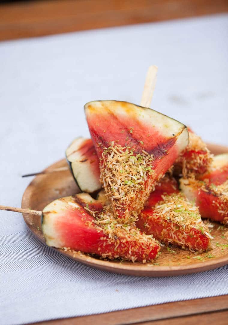 Grilled Watermelon on a Stick Glazed wedges of watermelon with agave, lime, chili and salt get dipped into crispy crackly coconut crust. cook time 5 min prep time 5 min dessert mexican serves 8 121 calories ¼ cup agave ¼ cup lime juice 2 tsp chili powder 1 tsp sea salt 1 medium watermelon, cut into 1 inch thick wedges 1/3 cup unsweetened shredded coconut 1 tbsp lime zest Soak 4 large popsicle sticks for at least an hour. In a small bowl, mix together the honey, lime juice, cayenne pepper and salt. In another small bowl, mix together the coconut and lime zest. Preheat the grill to medium high heat. Using a knife, carefully cut a small incision into the rind of the watermelon. Insert the popsicle stick into the hole. Brush both sides of the watermelon slices with the agave mixture and grill for about 2 minutes per side until deep grill marks appear. Remove from the heat, brush again with more of the mixture, then dip into the coconut lime mixture.