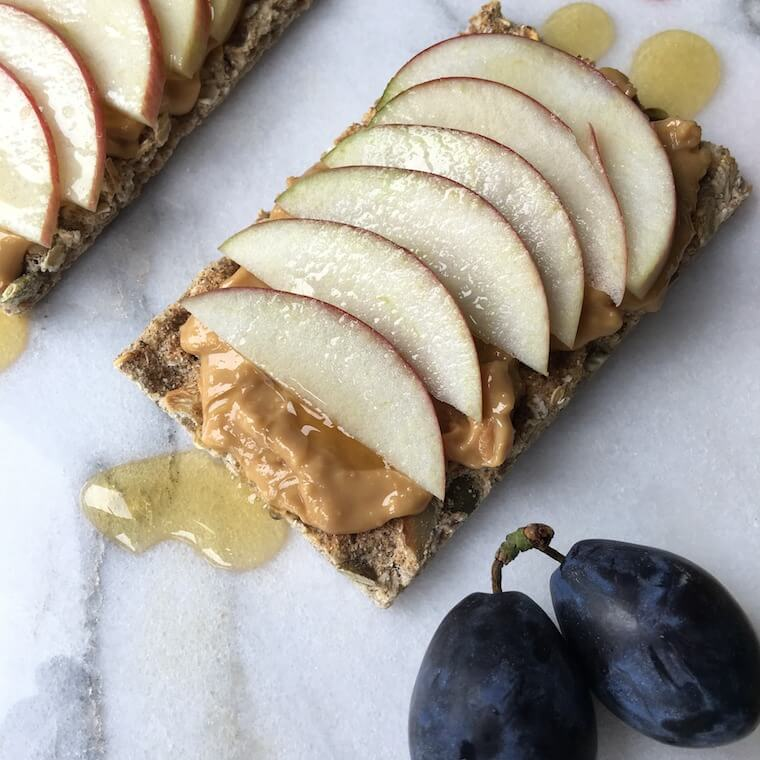 Overhead photo of a cracker with nut butter and sliced apple.