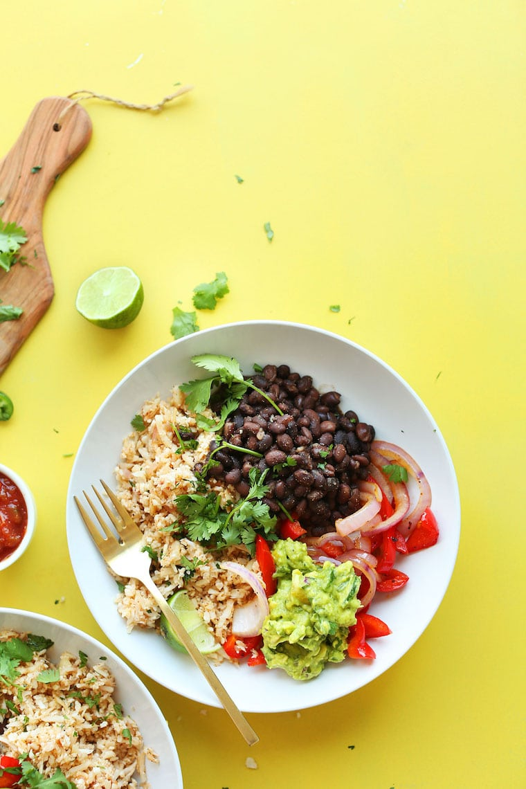 A white plate filled with beans, rice, veggies and guacamole on a bright yellow surface.