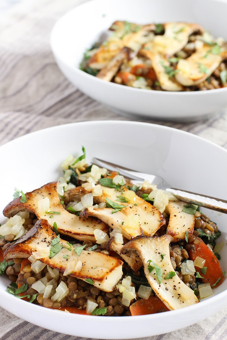 Cooked lentils in two white bowls topped with oyster mushrooms.