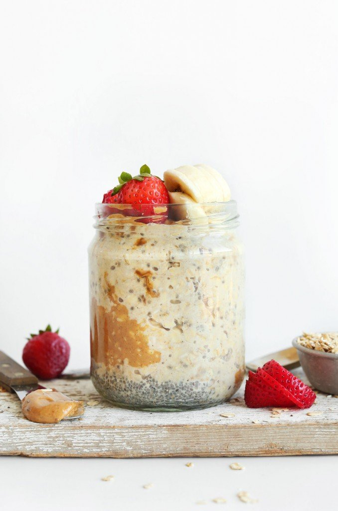 Overnight oats in a glass jar, topped with peanut butter, bananas and strawberries.
