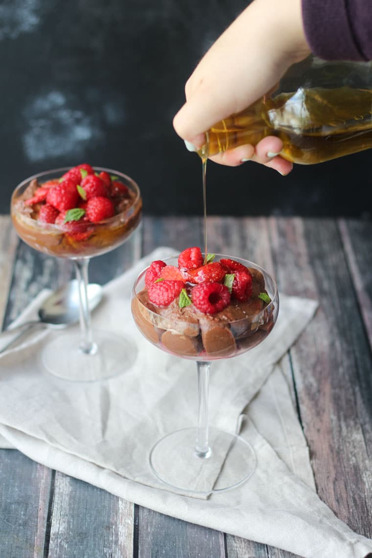 two clear dishes filled with vegan chocolate olive oil mousse garnished with macerated berries