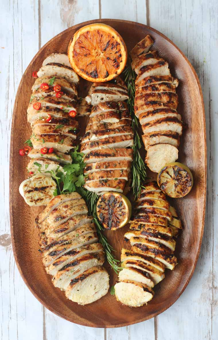 birds eye view of grilled marinated chicken breasts five ways on a wooden serving board