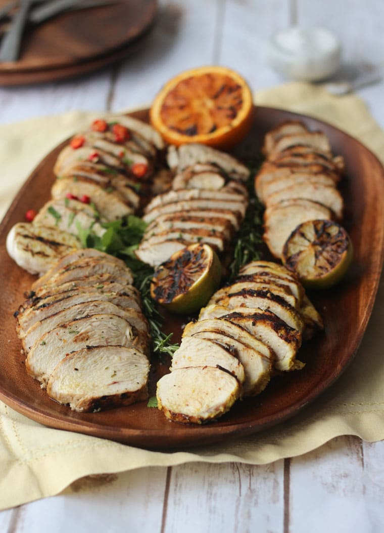 five flavours of grilled and marinated chicken breasts on a wooden serving board