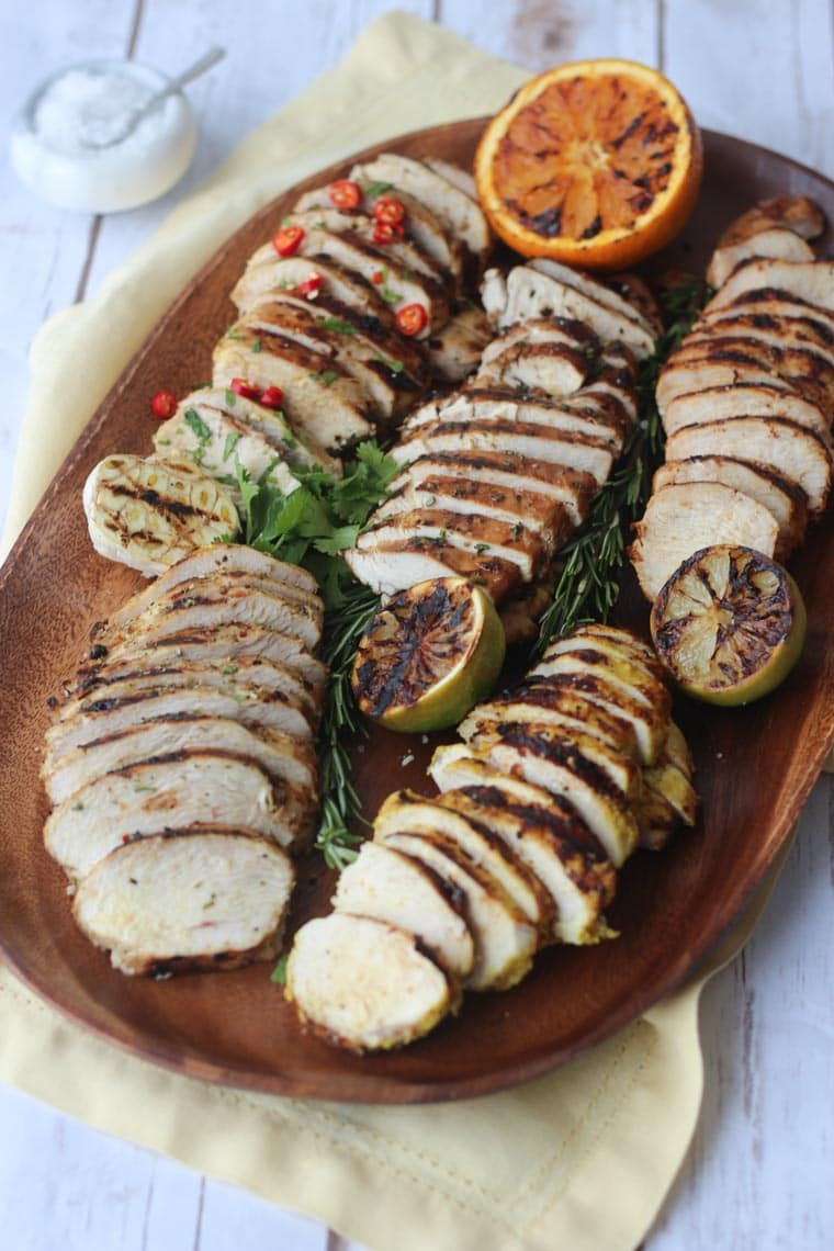 grilled chicken breasts five different ways on a wooden serving board