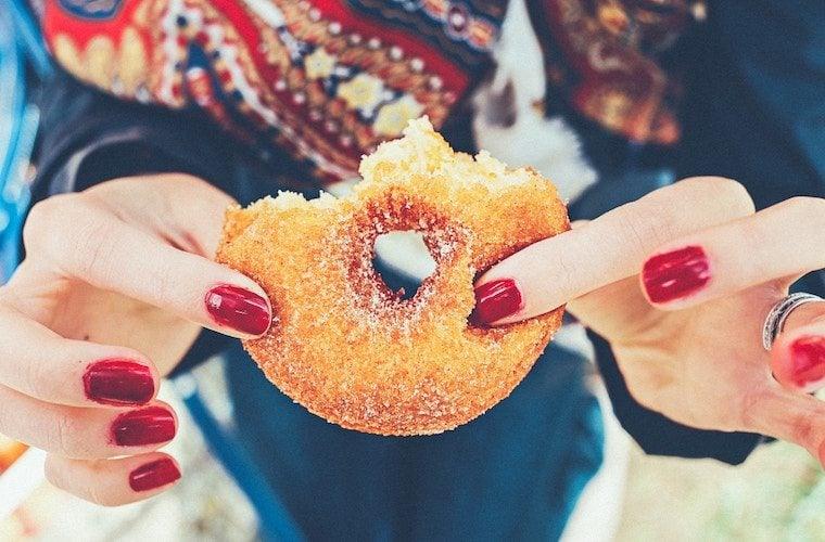 A close up of a person holding a doughnut.