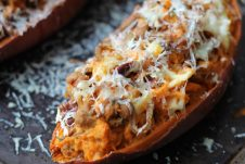 A close up of a baked sweet potato with caramelized onion and apple.