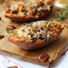 A close up of a baked sweet potato with caramelized onion and apple on a brown cutting board.
