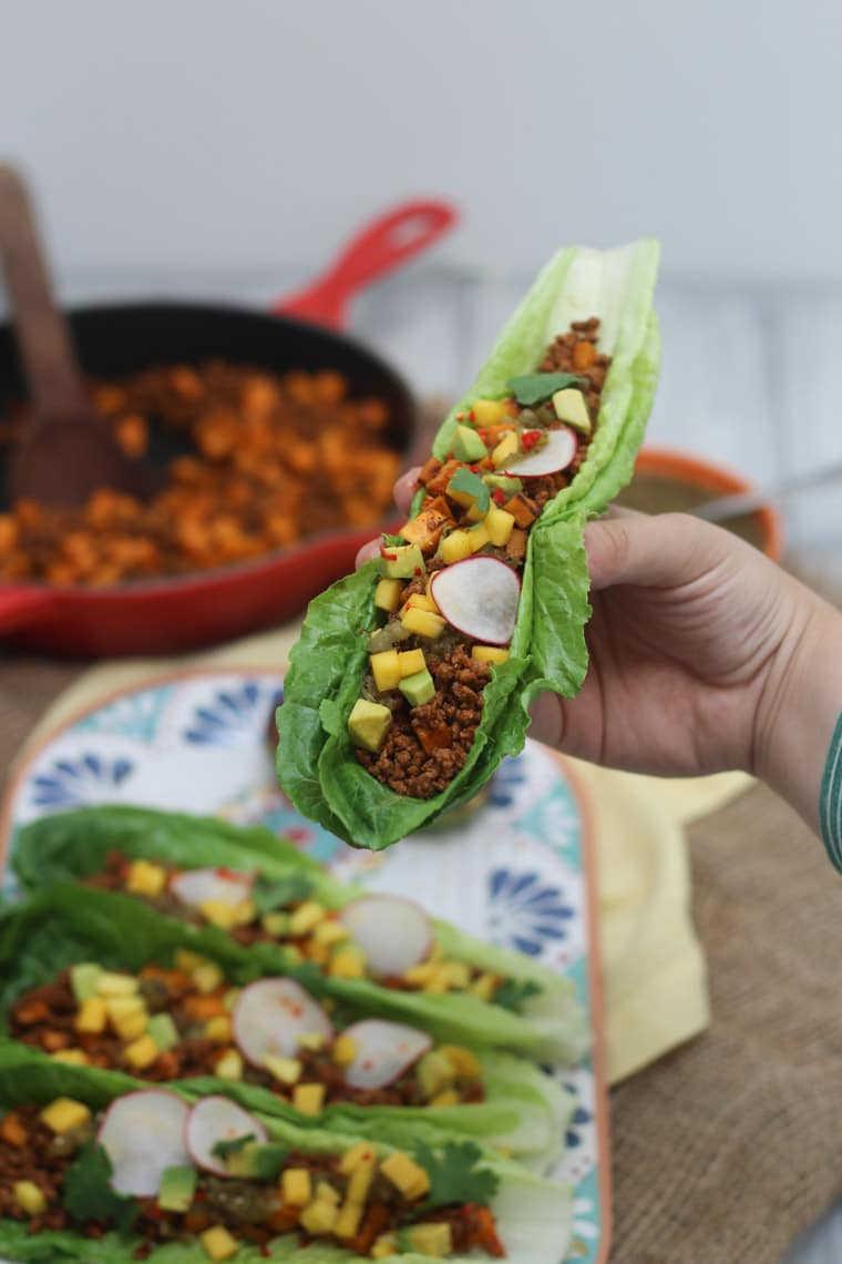 These low fat homemade chorizo and sweet potato tacos are packed with flavour, served in low carb lettuce wraps, and topped with avocado, mango and radishes.