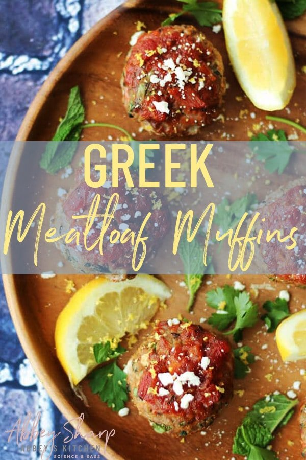 close up of greek flavoured mini meatloaf muffins on a wooden plate garnished with lemon and parsley