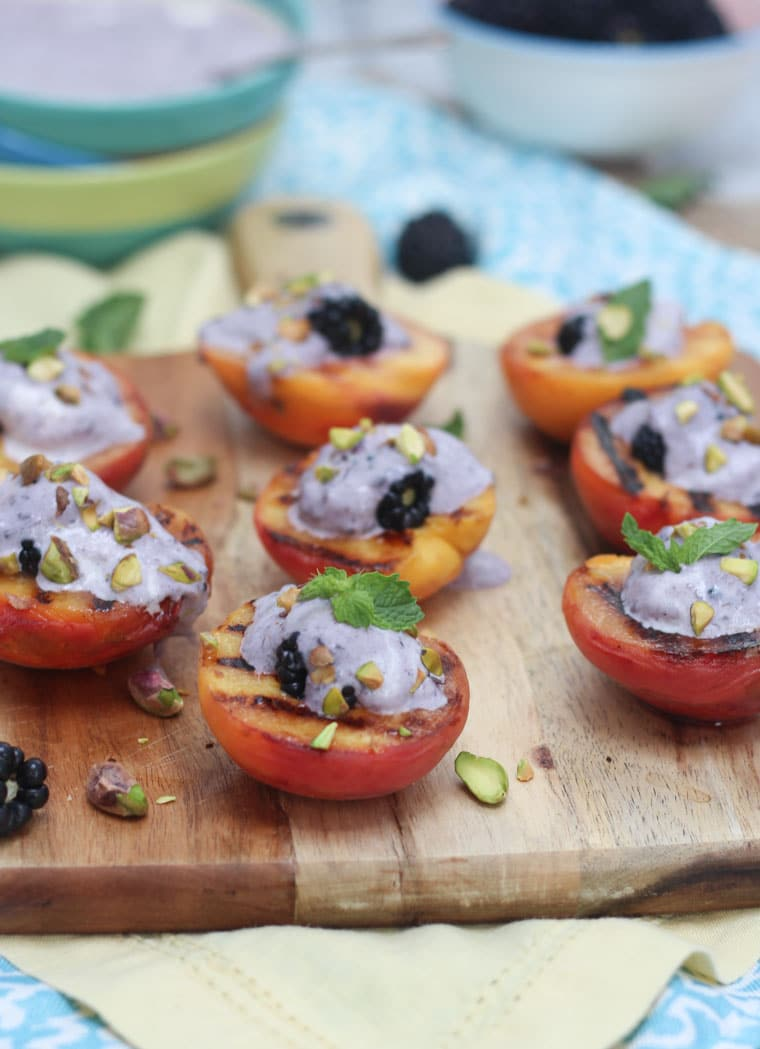 vegan grilled peaches with blackberry coconut cream garnished with pistachios and mint