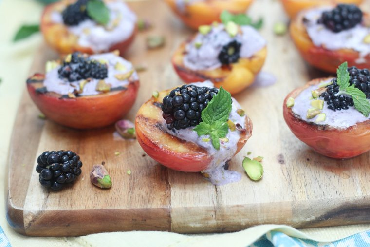 close up of vegan grilled peaches topped with blackberry coconut cream on a wooden board