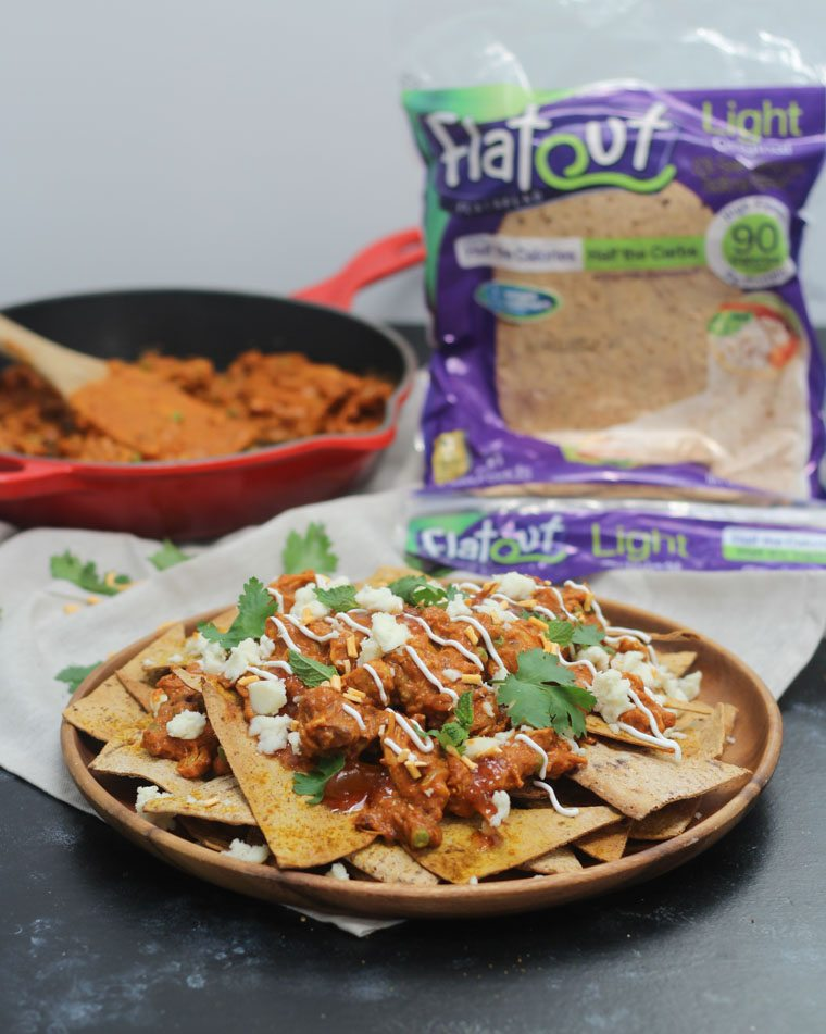 A photo of butter chicken nachos with flatout bread in the background and a skillet of the chicken.