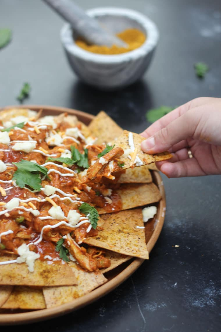 A hand lifting up a chip from a plate of butter chicken nachos.