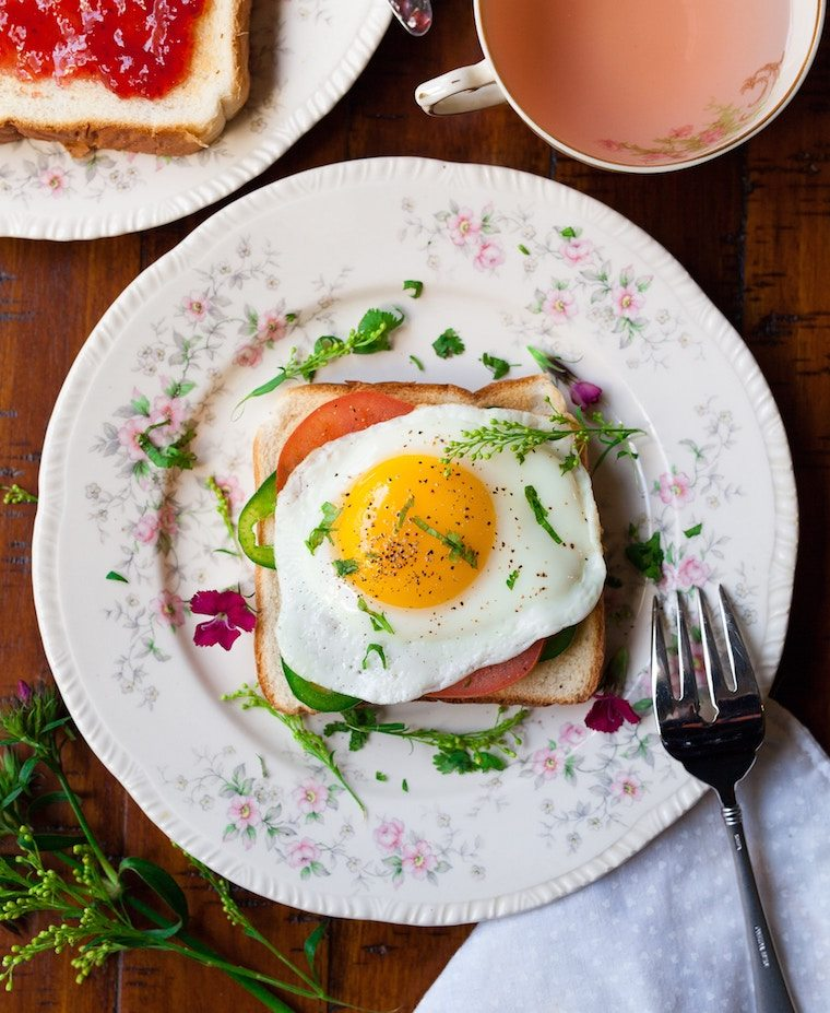 A plate on a table with a toast with an egg on top.