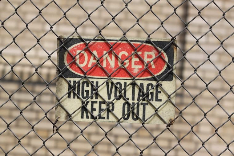 high voltage danger sign and a fence