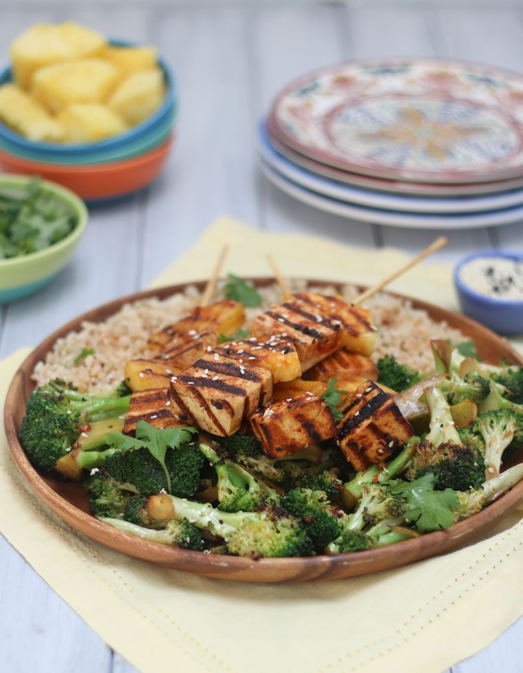 dinner plate filled with spicy tofu and pineapple skewers, rice, and greens