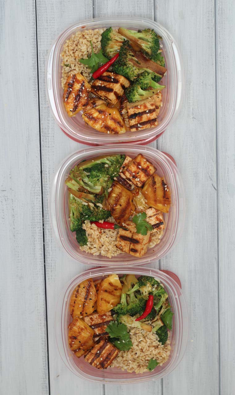 birds eye view of spicy grilled tofu and pineapple skewers in containers for meal prep