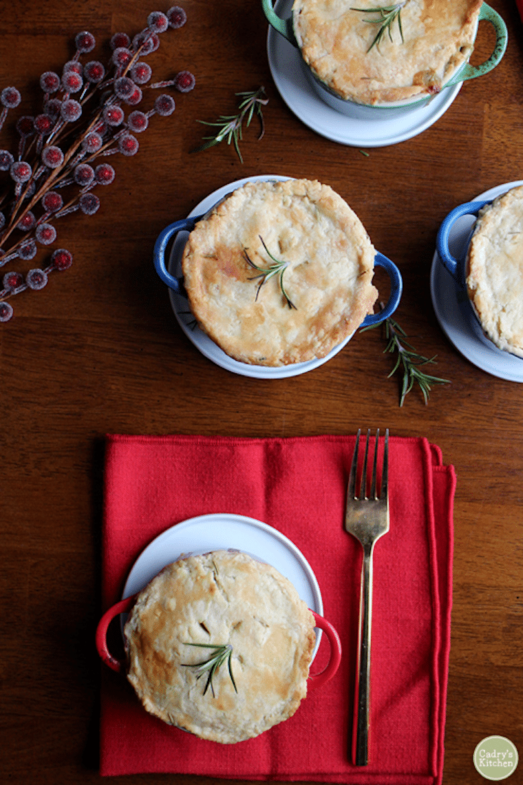 birds eye view of multiple vegetable pot pies garnished with fresh herbs on a wooden table