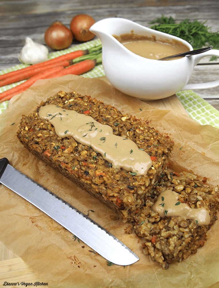 two slices of lentil loaf drizzled with cashew gravy on parchment paper