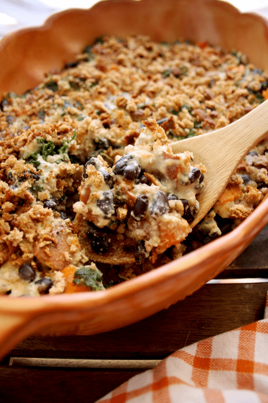 close up image of vegan sweet potato casserole in an orange casserole dish with a wooden spoon inside