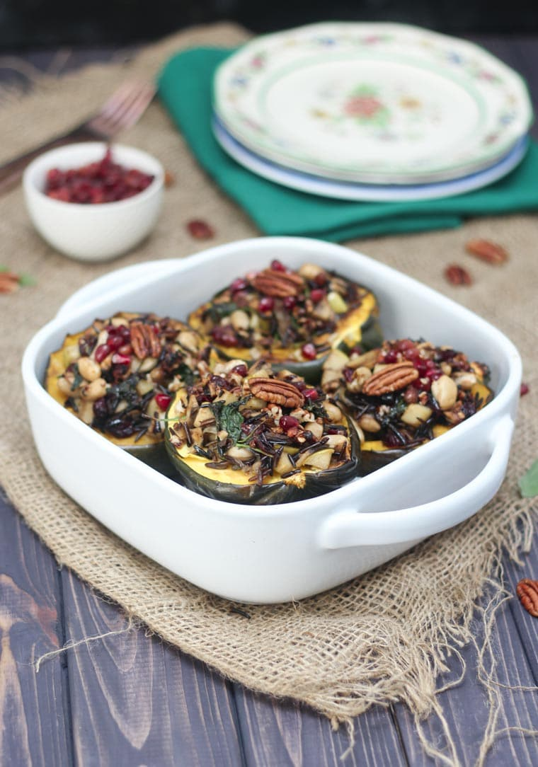 Stuffed acorn squash in a white casserole dish.
