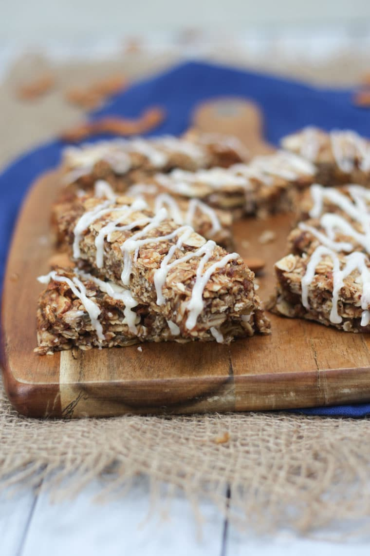 A close up image of multiple cinnamon bun granola bars on a brown cutting board.