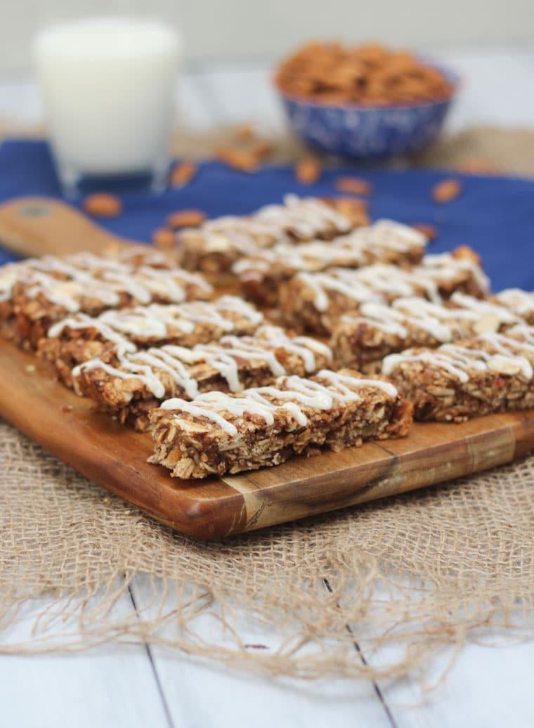 An angled image of multiple cinnamon bun granola bars on a brown cutting board.