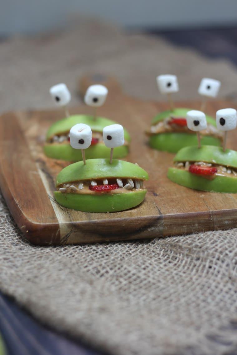 Four halloween apple alien smiles with marshmallow eyes.