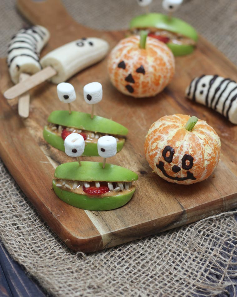 various vegan and gluten free halloween fruit treats on a wooden board