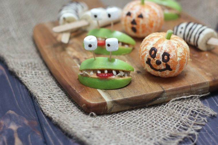 close up of various halloween themed fruit treats on a wooden serving board