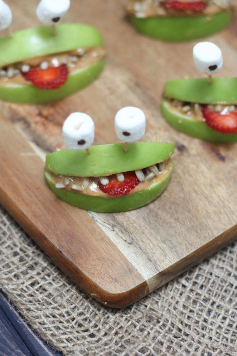 Close up of halloween apple alien smiles on a cutting board.