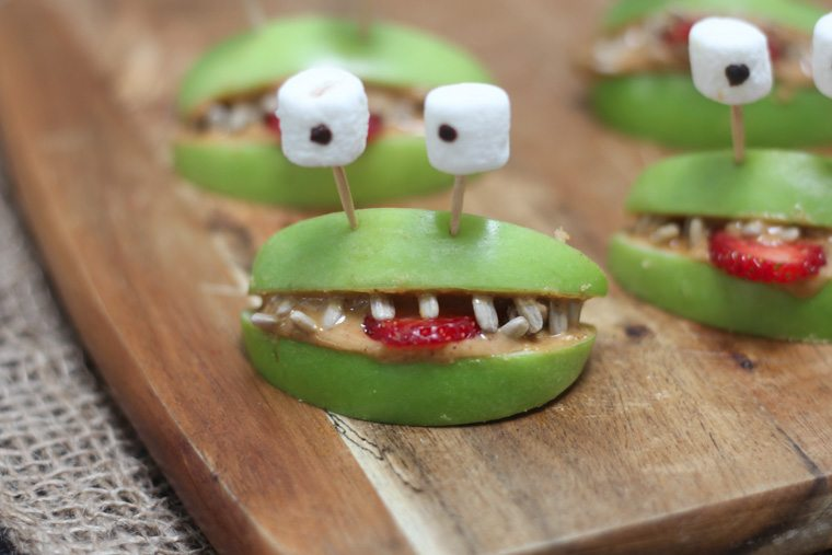 A close up of halloween apple alien smiles with marshmallow eyes.