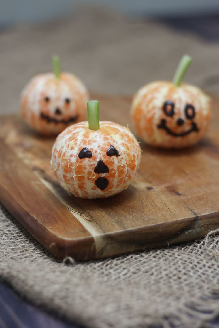 close up of three clementine pumpkins on a wooden board